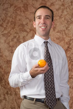 Employee With Orange stock photo, A smiling employee wearing a shirt and tie is holding an orange by Richard Nelson
