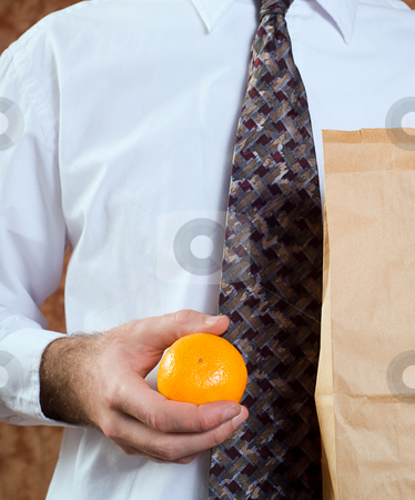 Healthy Orange Snack stock photo, Closeup of a businessman holding his paper bagged lunch and an orange by Richard Nelson
