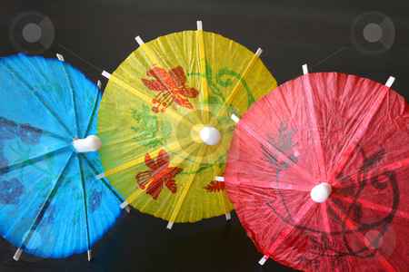Cocktail Umbrellas stock photo, Blue, yellow and red Cocktail Umbrellas on a dark surface by Vanessa Van Rensburg