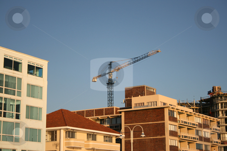 Crane stock photo, Building Crane behind other buildings with construction to the right by Vanessa Van Rensburg