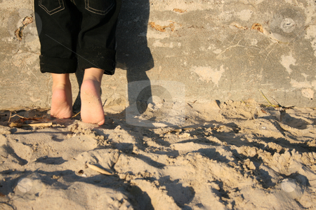 Tippie Toes stock photo, Toddler standing on the beach against a wall on his tippie toes