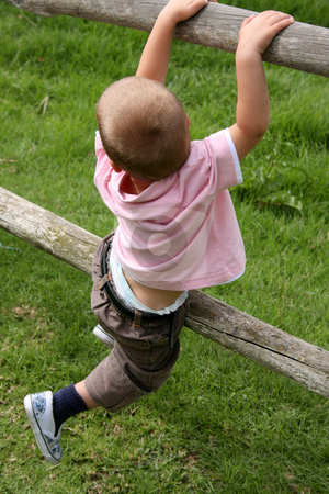 Young Climber stock photo, Young boy climbing on wooden fencing on a farm by Vanessa Van Rensburg
