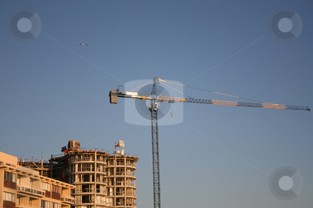 High Crane stock photo, High Crane against a blue sky close to a building siteBuilding Crane behind other buildings with construction to the right by Vanessa Van Rensburg