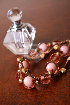 Jewelery stock photo, Beaded Jewelery on a brown surface with a glass bottle by Vanessa Van Rensburg
