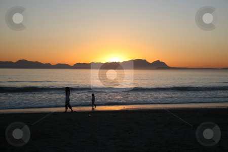 Sunset stock photo, Mother & Daughter walking on the beach as the sun sets by Vanessa Van Rensburg