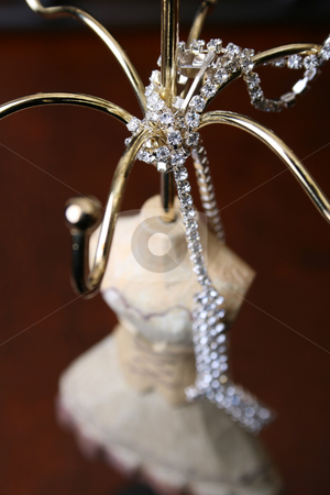 Diamonds stock photo, Diamond Necklace draped over a wooden jewelery stand by Vanessa Van Rensburg