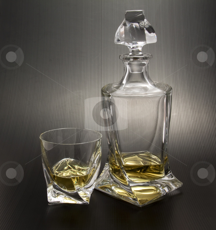Whisky stock photo, Crystal bottle and glass with light whisky on black background by Fabio Alcini
