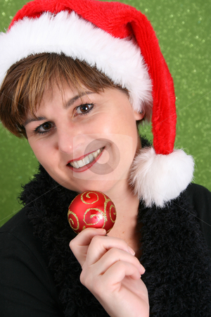 Christmas Decoration stock photo, Adult female wearing a christmas hat, holding a decoration by Vanessa Van Rensburg