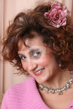 Friendly Female stock photo, Mature female with a friendly expression, a rose in her hair by Vanessa Van Rensburg
