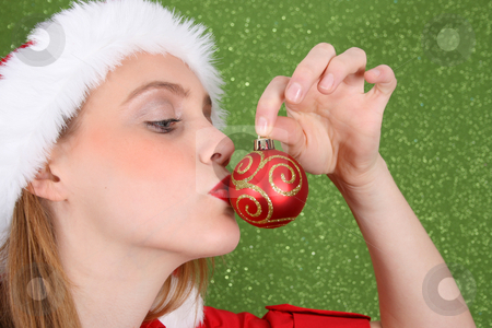 Christmas Decoration stock photo, Christmas girl kissing a red and gold decoration by Vanessa Van Rensburg