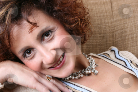 Mature female stock photo, Mature female, lying on a sofa, wearing beautiful jewelery by Vanessa Van Rensburg