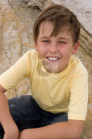 Childhood Happiness stock photo, Happy boy casually sitting against sandstone background. by Leah-Anne Thompson