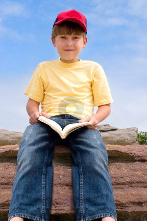 Sitting Boy with Book stock photo, Child holding a book sitting against blue sky by Leah-Anne Thompson