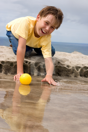 Happily Playing stock photo, Happy child playing and splashing with yellow ball by Leah-Anne Thompson