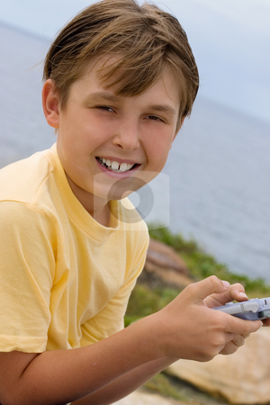 Child with handheld game stock photo, Child holding a portable game player and smiling to the viewer. by Leah-Anne Thompson