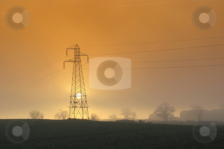 Setting sun with pylon stock photo, The sun setting behind a pylon on a hillside on a misty winter evening by Mike Smith