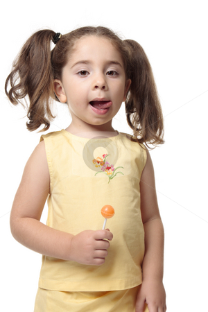 Little girl licking lips delicious stock photo, A little girl licks her lips.  She iis wearing a yellow outfit with hair in ponytails and she is holding a candy lollipop by Leah-Anne Thompson