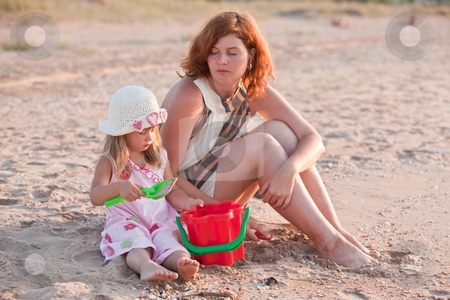 Mother and daughter stock photo, People series: little girl and her mother on sea beach by Gennady Kravetsky
