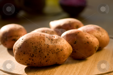 Potatoes stock photo, Food series: some raw potatoes on the wooden board by Gennady Kravetsky