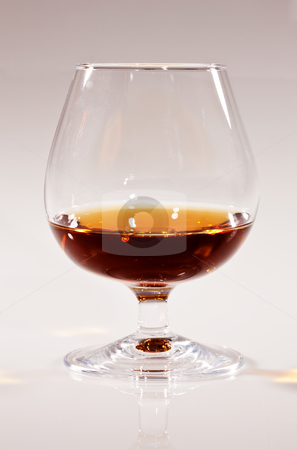 Cognac stock photo, Drink series: glass of cognac over light background by Gennady Kravetsky