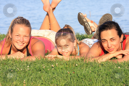 Girls portrait stock photo, Three joyful girls are lying prone on the shore by ARPAD RADOCZY