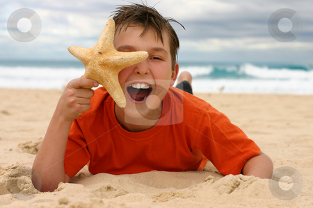 Laughing boy with starfish on the beach stock photo, Ecstatic child lying on the beach holding a starfish to face. by Leah-Anne Thompson