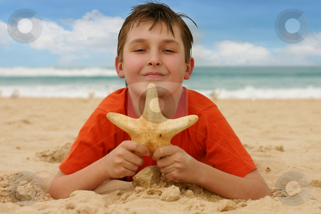 Boy on beach holding a sea star stock photo, Child on sandy beach holds a starfish - focus on boy only.