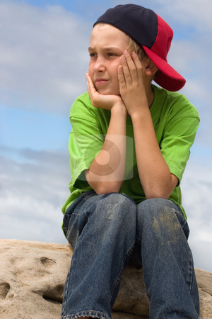 Child in cap looking sideways stock photo, A nine year old boy on a rock looking sideways by Leah-Anne Thompson