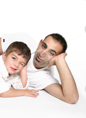 Father and son relaxing stock photo, Dad on floor with cheeky son winking one eye, space for text. by Leah-Anne Thompson