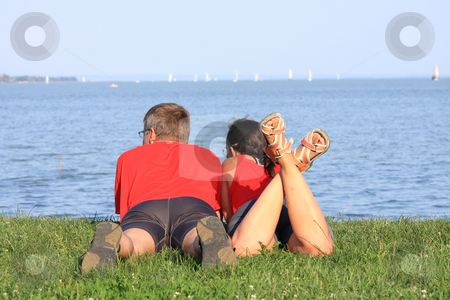 Young couple stock photo, Young couple is laying by the shore of the lake by ARPAD RADOCZY