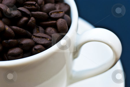 Cup of coffee stock photo, A white cup full of roasted coffee beans by bah1969