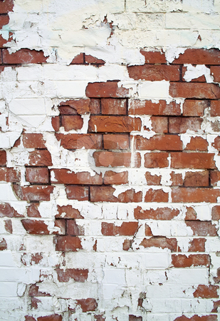 White paint peeling off a red brick wall. stock photo, White paint peeling off a red brick wall. by Stephen Rees