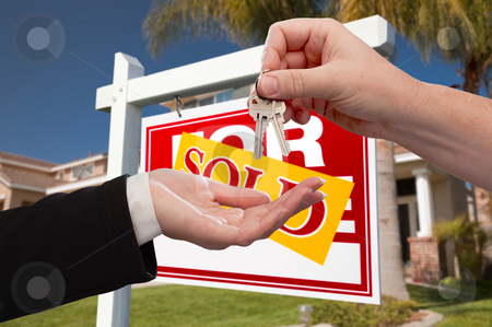 Agent Handing Over the Key to a New Home stock photo, Agent Handing Over the Key to a New Home with Real Estate Sign and House in the Background. by Andy Dean