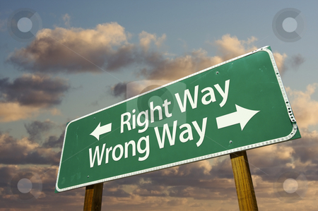 Right and Wrong Way Green Road Sign stock photo, Right and Wrong Way Green Road Sign with dramatic blue sky and clouds. by Andy Dean