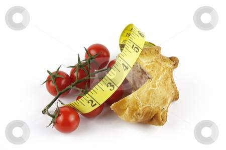 Tomatoes and Pork Pie with Tape Measure stock photo, Contradiction between healthy food and junk food using tomatoes and a pork pie with a tape measure on a reflective white background by Keith Wilson
