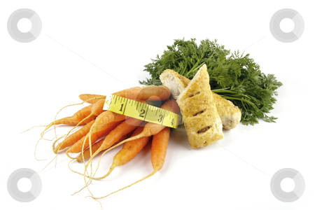 Carrots and Sausage Roll with Tape Measure stock photo, Contradiction between healthy food and junk food using bunch of carrots and sausage roll with a tape measure on a reflective white background by Keith Wilson