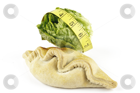 Salad Lettace with Pasty and Tape Measure stock photo, Contradiction between healthy food and junk food using a green salad lettace and pasty with a yellow tape measure on a reflective white background by Keith Wilson