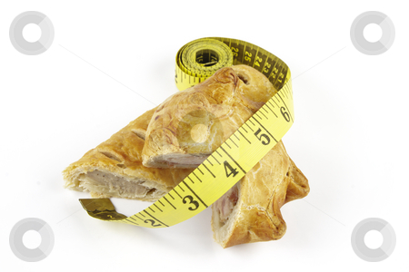 Sausage Roll with Pork Pie and Tape Measure stock photo, Single golden sausage roll cut in half with pork pie and yellow tape measure on a reflective white background by Keith Wilson