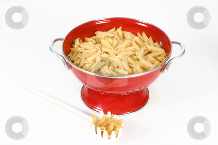 Pasta shells in colander stock photo, Penne pasta shells (uncookded) sitting  in a red colander with a white plastic pasta spoon laid beside on a white background. by Leah-Anne Thompson