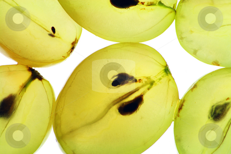 Transparent slices of ripe grapes stock photo, Translucent half of ripe juicy yellow green grapes. Isolated on white. by Aleksandr Volokov