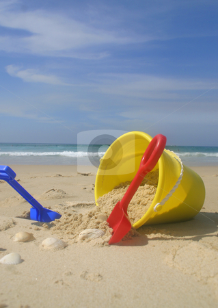 Beach bucket and spades. stock photo, A childs yellow beach bucket and spades.    Focus is on the bucket of  sand and spades.   A couple of the shells and beach is oof range. by Leah-Anne Thompson