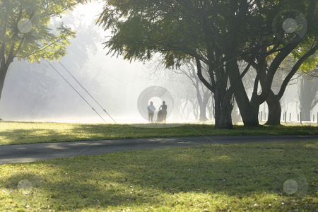Two Joggers stock photo, Two runners in the park on a misty morning by Leah-Anne Thompson