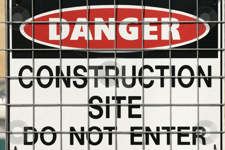 Construction warning sign stock photo, Warning sign on fence. by Leah-Anne Thompson