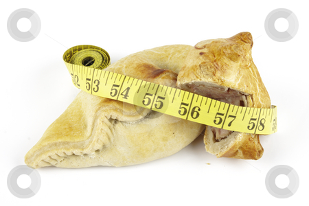 Pasty with Pork Pie and Tape Measure stock photo, Single golden pasty with pork pie and yellow tape measure on a reflective white background by Keith Wilson