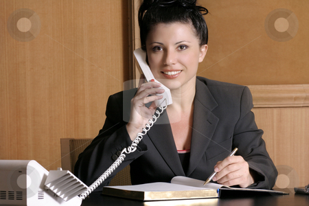 Executive on the phone stock photo, Professional woman at work desk on the phone. by Leah-Anne Thompson
