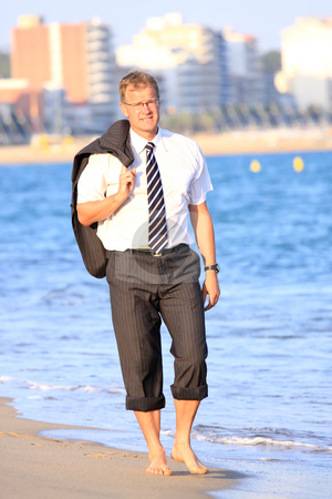 Businessman stock photo, Happy young businessman walks close to the sea by ARPAD RADOCZY