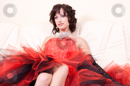 Woman in a red dress stock photo, Woman in a red dress posing in the interior by Artem Zamula