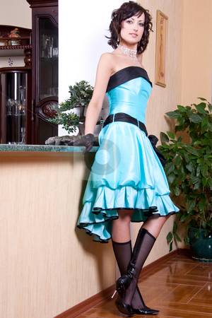 Woman in a blue dress stock photo, Woman in a blue dress posing in the interior by Artem Zamula
