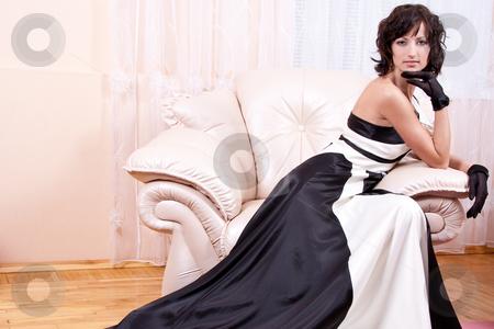Woman in black and white dress stock photo, Woman in black and white dress posing in an armchair by Artem Zamula