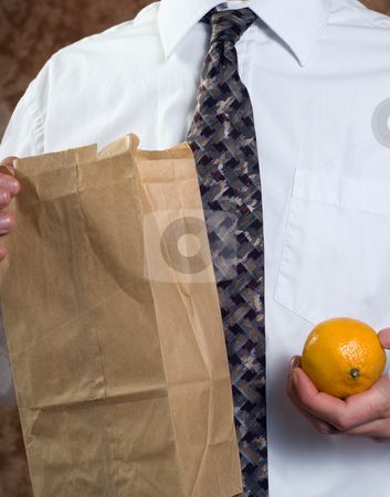 Healthy Lunch stock photo, Closeup businessman showing off his healthy lunch featuring a paper bag and a fresh orange by Richard Nelson